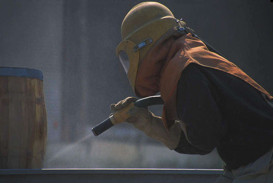 Worker surrounded by flying debris sandblasting wooden barrel preparing it for use.